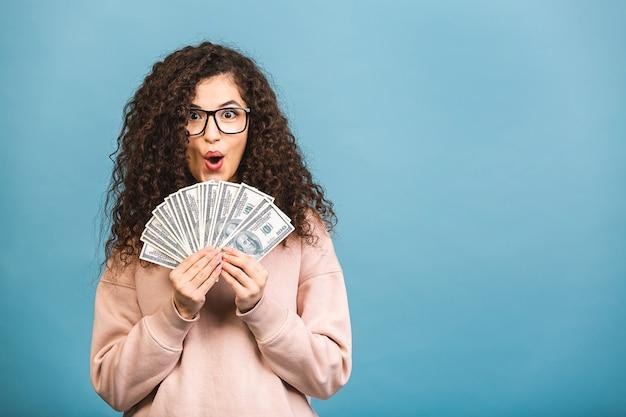 Szczęśliwy zwycięzca! portret wesoła młoda kobieta kręcone, trzymając banknoty pieniądze i świętuje na białym tle na niebieskim tle.