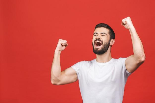 Szczęśliwy zwycięzca szczęśliwy młody przystojny mężczyzna gestykuluje usta i utrzymuje otwarty podczas gdy stojący przeciw czerwieni ścianie.
