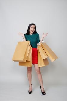 Szczęśliwych bożych narodzeń azjatycki kobieta zakupy trzyma papierowe torby