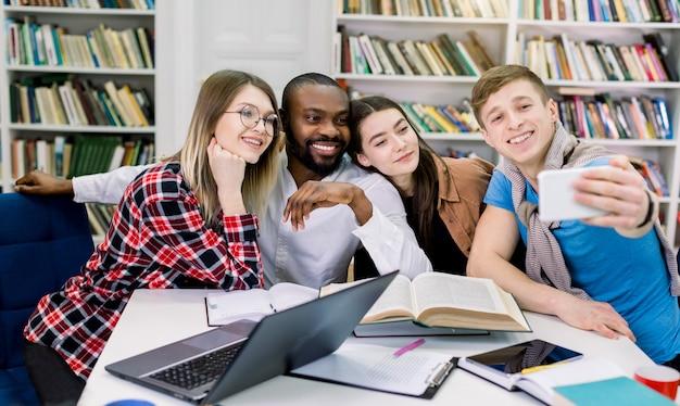 Szczęśliwych czterech wieloetnicznych studentów wykonujących śmieszne selfie w bibliotece podczas wspólnego studiowania. zabawna edukacja, akademia, szkoła