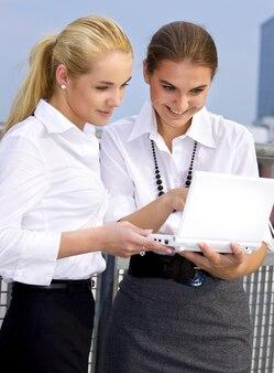 Szczęśliwych przedsiębiorców z laptopa w mieście