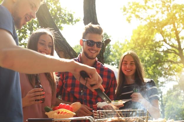 Szczęśliwych przyjaciół grillujących mięso i cieszących się grillem na świeżym powietrzu.
