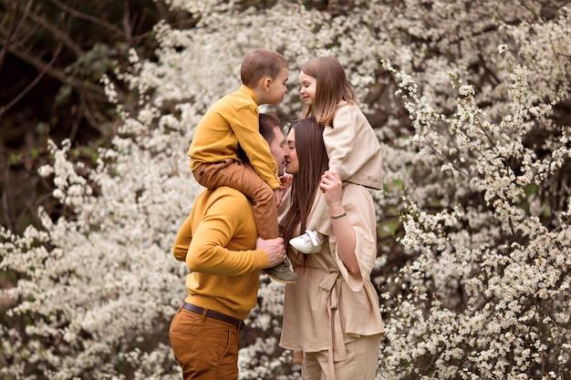 Szczęśliwych rodziców ciężarna mama i tata, córka i syn na tle kwitnących drzew.