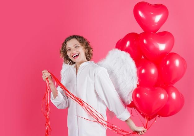 Szczęśliwych walentynek. anioł kobieta z balonów w kształcie czerwonego serca. uśmiechnięty amorek żeński ze skrzydłami.