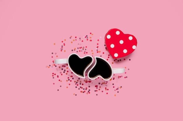 Szczęśliwych walentynek. filiżanki kawy w kształcie serca pudełko z konfetti na różu
