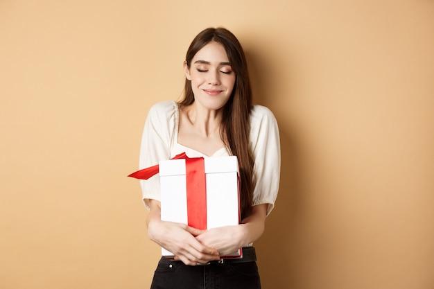 Szczęśliwych walentynek. marzycielska kobieta przytulająca prezent-niespodziankę, zamykająca oczy i uśmiech, stojąca na beżowym tle.