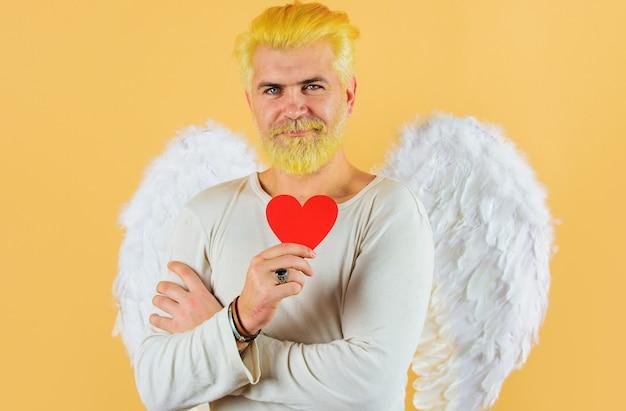 Szczęśliwych walentynek. męski anioł z czerwonym sercem. brodaty mężczyzna z białymi skrzydłami trzyma papierowe serce.