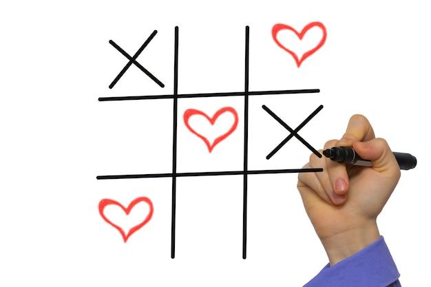 Szczęśliwych walentynek tic-tac-toe przez xoxo, ręka trzyma marker na białym tle na białych tablicach