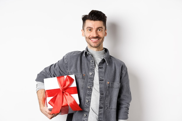 Szczęśliwych walentynek. uśmiechnięty przystojny mężczyzna przynosi prezent na romantyczną randkę, trzymając pudełko z prezentem i patrząc romantycznie na aparat, biały.