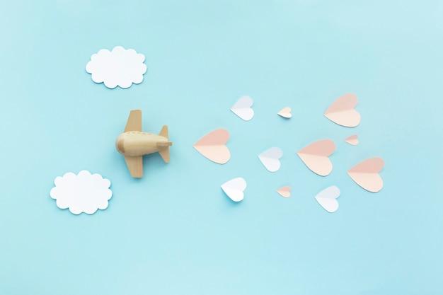 Szczęśliwych walentynek. zabawka samolot samolot na niebieskim tle z białymi chmurami i różowymi sercami.