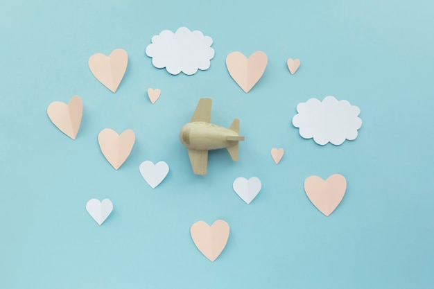 Szczęśliwych walentynek. zabawka samolot samolot na niebieskim tle z papierowymi białymi chmurami i papierowymi różowymi sercami.