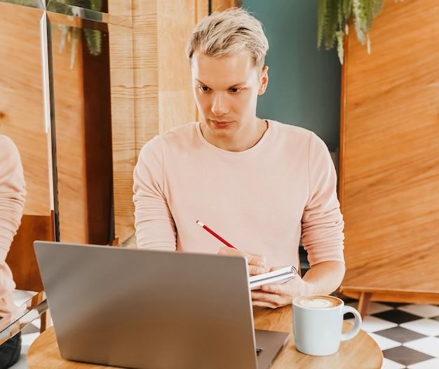 Szczęśliwym człowiekiem biznesu siedząc w stołówce z laptopem. biznesmen pracujący, sprawdzający pocztę e-mail na komputerze