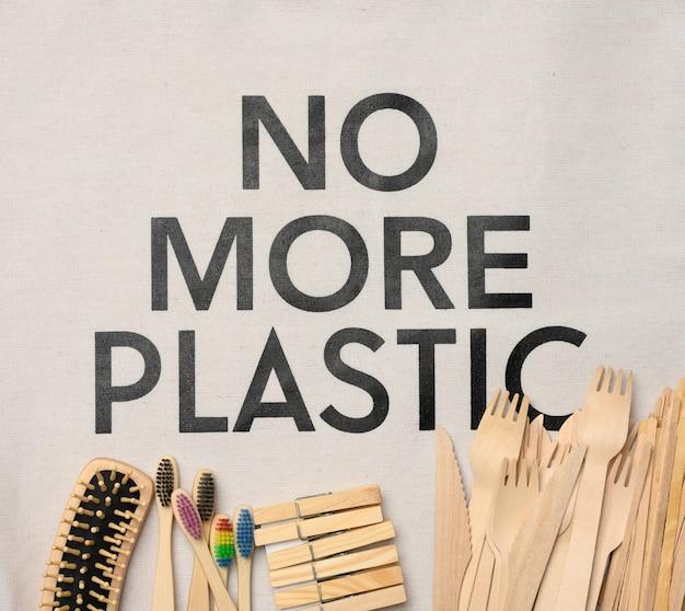 Szczoteczka do zębów, grzebień, spinacz do bielizny i inne drewniane przedmioty na białej powierzchni, widok z góry, koniec z plastikiem