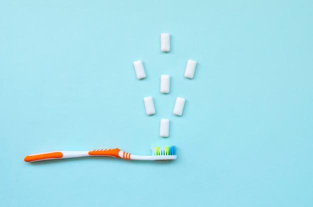 Szczoteczka do zębów i gumy do żucia leżą na pastelowym niebieskim tle. t