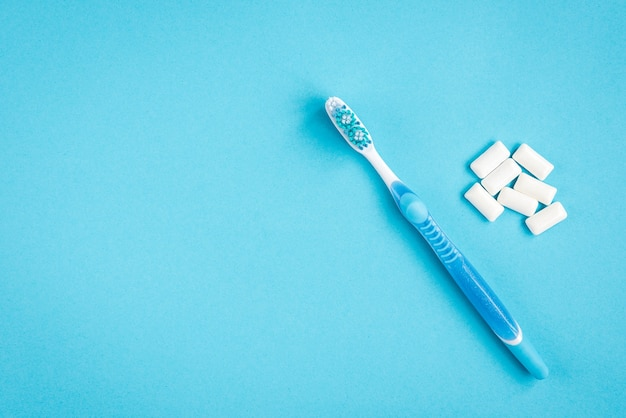 Szczoteczka do zębów, nici dentystyczne i dziąsła na niebieskim tle. czyszczenie i ochrona zębów