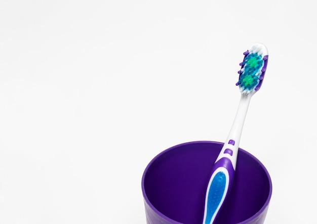 Szczoteczka z plastikową szklanką z miejscem na tekst, koncepcja pielęgnacji zębów dziecka i profilaktyka próchnicy