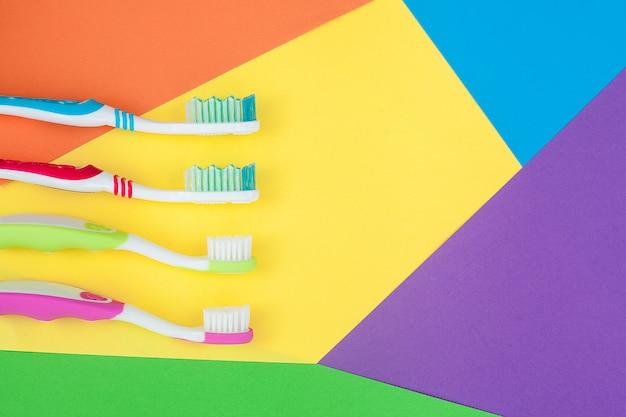 Szczoteczki do zębów na kolorowe jasne tło. koncepcja higieny rodziny.