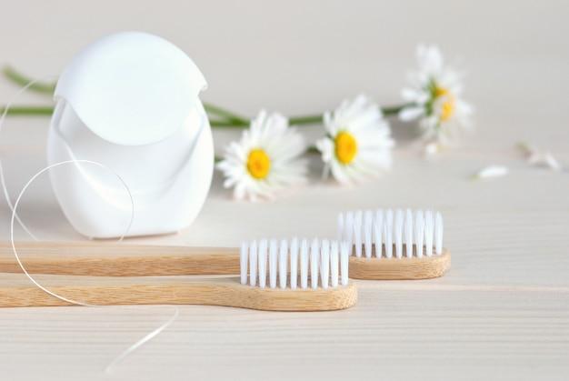 Szczoteczki do zębów, nici dentystyczne i białe stokrotki, miejsce na kopię copy