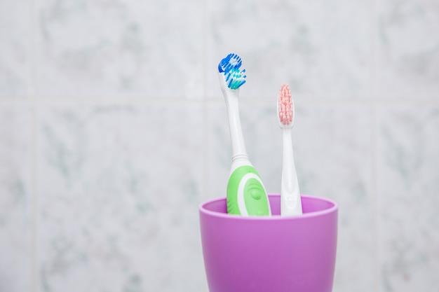 Szczoteczki do zębów w plastikowej fiołkowej filiżance w łazience. elektryczne i zwykłe szczoteczki do zębów. porównanie.