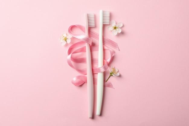 Szczoteczki do zębów, wstążki i kwiaty na różowym tle, miejsce na tekst