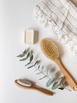 Szczotka do ciała z drewnianym uchwytem, pumeksem, wiklinowym pudełkiem, białym ręcznikiem i mydłem