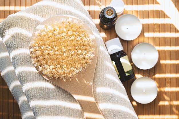 Szczotka do kąpieli z olejkami eterycznymi i świecami z bliska. koncepcja spa.