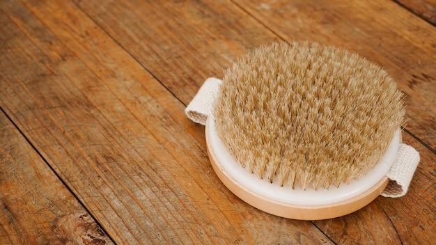 Szczotka do masażu na sucho wykonana z naturalnych materiałów na drewnianym tle. minimalizm, kopia przestrzeń.