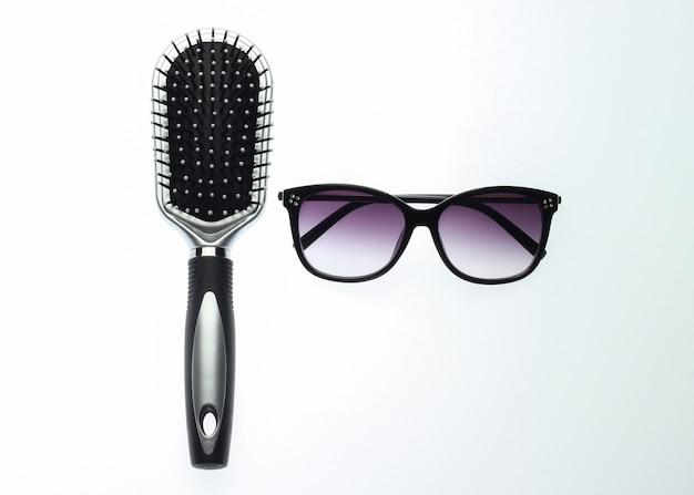 Szczotka do włosów i okulary na białym tle. akcesoria damskie