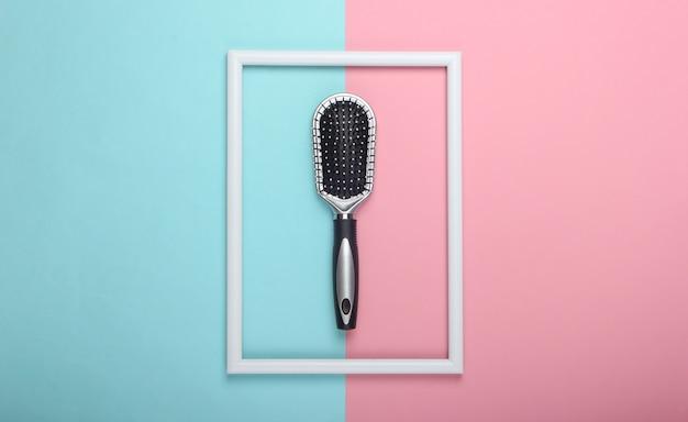 Szczotka do włosów na różowo-niebieskiej pastelowej powierzchni z białą ramką