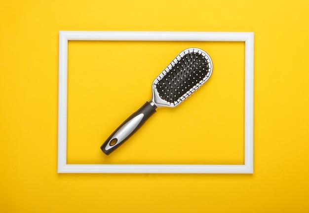 Szczotka do włosów na żółtej powierzchni z białą ramką