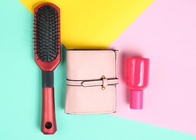 Szczotka do włosów, torebka, butelka perfum na kolorowym pastelowym tle. widok z góry. minimalizm