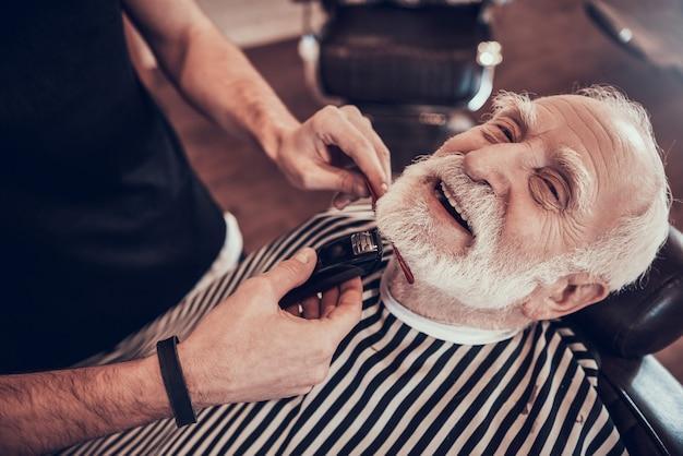 Szczotka do włosów w rękach młody człowiek w zakładzie fryzjerskim