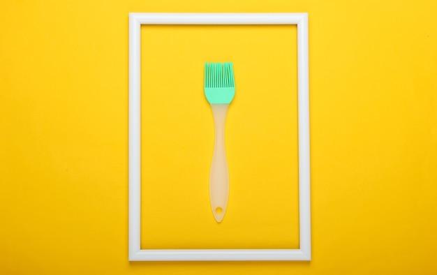 Szczotka kuchenna na żółtej powierzchni z białą ramką