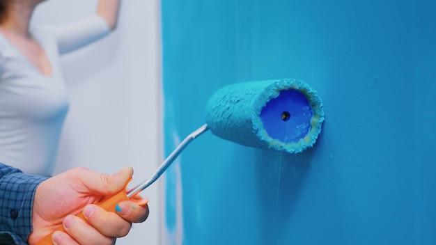 Szczotka rolkowa na ścianie podczas dekoracji wnętrz. przeróbka mieszkania. dekoracja domu i remont w przytulnym mieszkanku, naprawa i metamorfoza