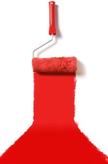 Szczotka rolkowa z czerwoną farbą na białym tle