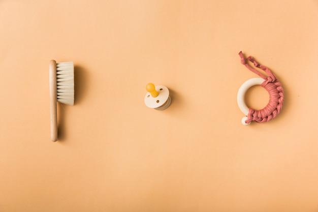 Szczotka; smoczek i zabawka na pomarańczowym tle