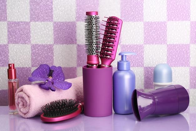 Szczotki do włosów, suszarka do włosów i butelki kosmetyczne w łazience
