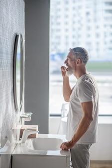 Szczotkowanie zębów. profil brodaty dorosły mężczyzna stojący przed umywalką, szczotkując zęby w pobliżu lustra
