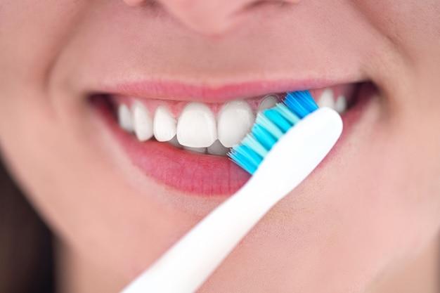 Szczotkowanie zębów za pomocą ultradźwiękowej elektrycznej szczoteczki do zębów z bliska. higiena jamy ustnej i pielęgnacja zębów