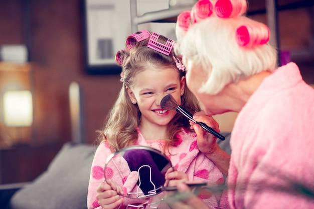 Szczotkuj nos. śliczna mała dziewczynka uśmiecha się podczas robienia makijażu z babcią, która ma pędzel do kosmetyków na nosie