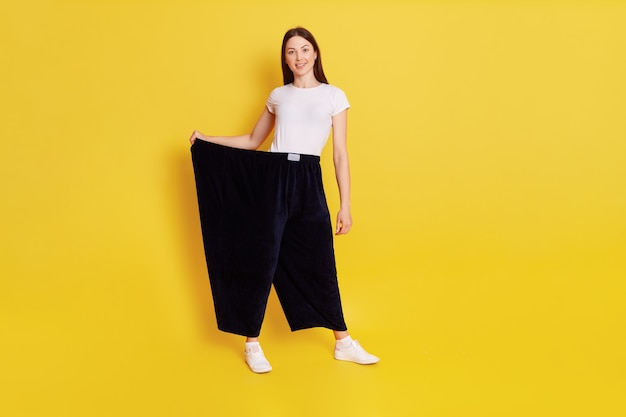 Szczupła, atrakcyjna dziewczyna o ciemnych włosach, ubrana w białą, kaukaską koszulkę i zbyt duże czarne spodnie, kobieta straciła na wadze i będąc z tego dumna, uśmiecha się do kamery, odizolowana na żółtej ścianie.