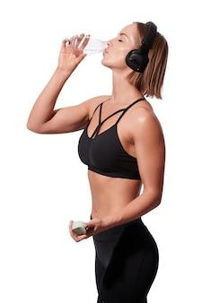 Szczupła atrakcyjna kobieta w odzieży sportowej z wodą do picia ręczników po treningu na białym tle na białym tle