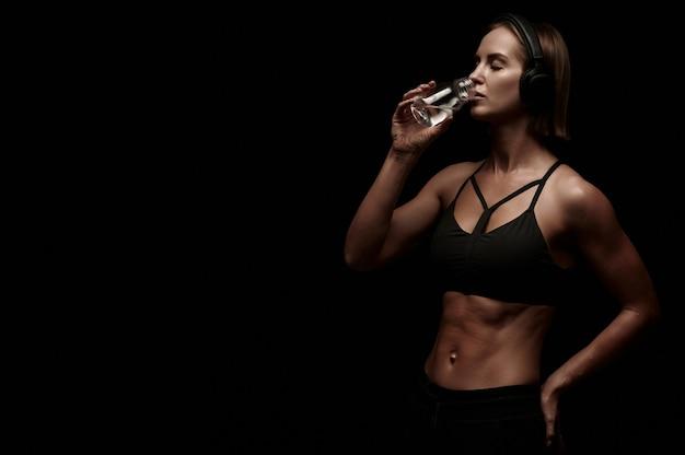 Szczupła atrakcyjna kobieta w odzieży sportowej z wodą do picia ręczników po treningu na czarnym tle na białym tle