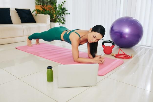 Szczupła azjatka stojąca w pozycji deski podczas wykonywania samouczka fitness na ekranie laptopa