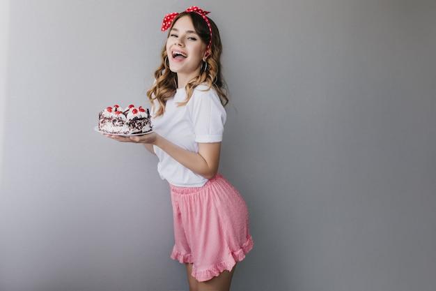 Szczupła biała dama w romantycznym stroju z tortem urodzinowym. kryty zdjęcie spektakularnej dziewczyny uśmiechającej się przed imprezą.