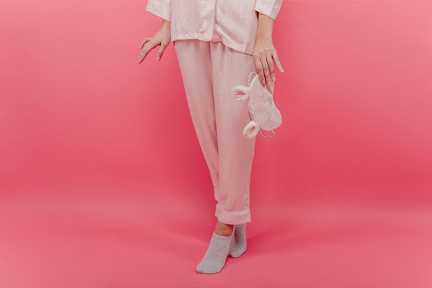 Szczupła biała dziewczyna w uroczych skarpetkach stoi na palcach i trzyma maskę do spania. wewnątrz zdjęcie ładnej kobiety w bawełnianej koszuli nocnej z maską na oczy pozującej na różowej ścianie.