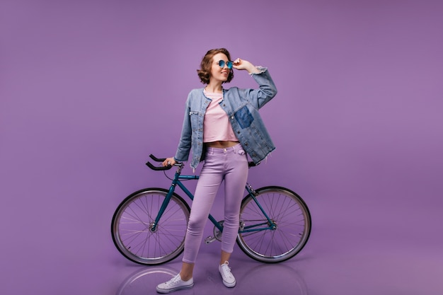 Szczupła blithesome kobieta pozuje z rowerem. kryty ujęcie pełnej długości kręconej modelki w fioletowych spodniach.