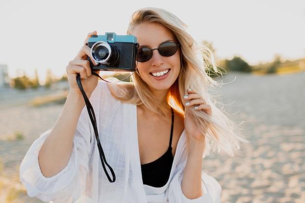 Szczupła blond szczęśliwa kobieta trzyma aparat retro i zabawę na ciepłej słonecznej plaży. koncepcja wakacji i podróży. naturalne piękno, wakacje w azji. modne okulary przeciwsłoneczne, biały strój.