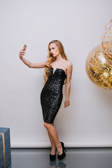 Szczupła blondynka w modnej czarnej sukience co selfie obok balonu z helem na przyjęciu urodzinowym. kryty pełnej długości portret młodej kobiety z kręcone fryzury, pozowanie podczas obchodów nowego roku.