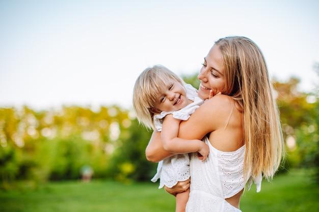 Szczupła blondynki kobieta bawić się z jej małą córką w lato parku. dziewczyny w białych sukienkach, wygląd rodzinny.